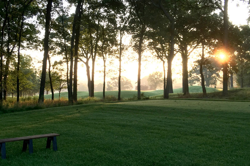 ArrowHead Golf Course during sun set with trees and a bench